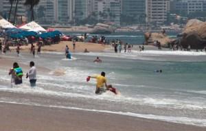 Un salvavidas ayuda a salir del mar a un turista que fue arrastrado por el fuerte oleaje, causado por el fenómeno de mar de fondo en la playa El Morro. Foto: Carlos Alberto Carbajal
