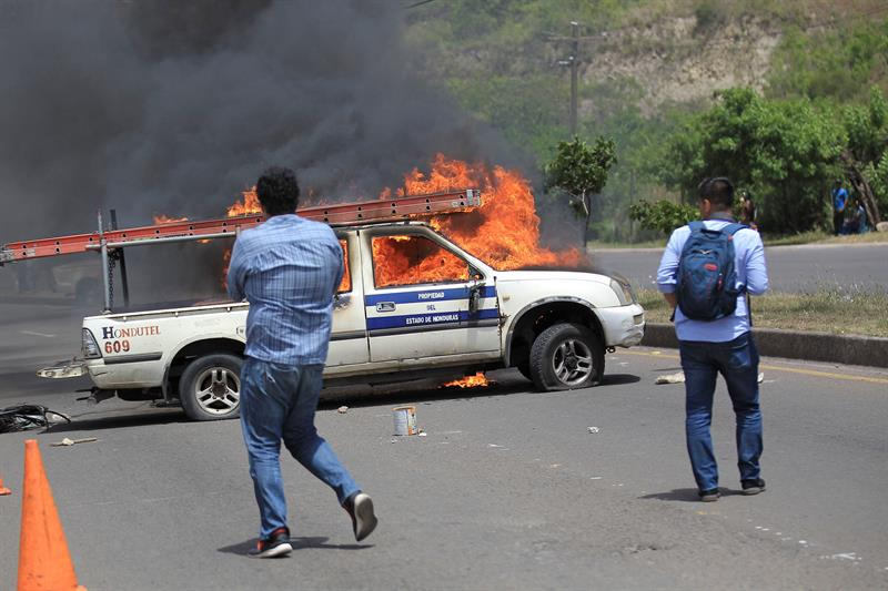 Fotografía con fecha 19 de julio de 2018, de un automóvil estatal quemado por protestantes durante el paro nacional de transporte. EFE