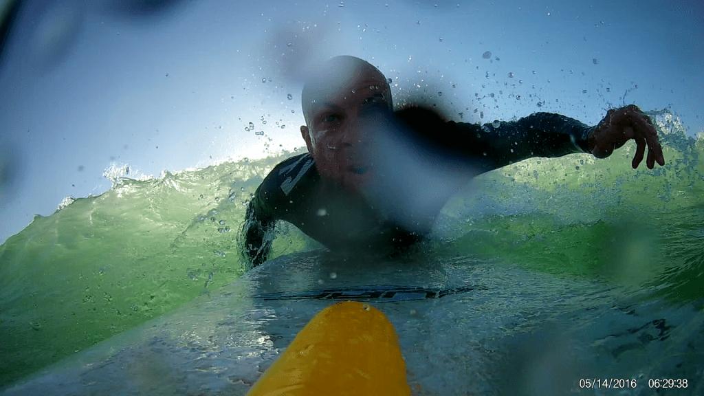 Волна накрыла серфера и он падает с гребня носом вниз