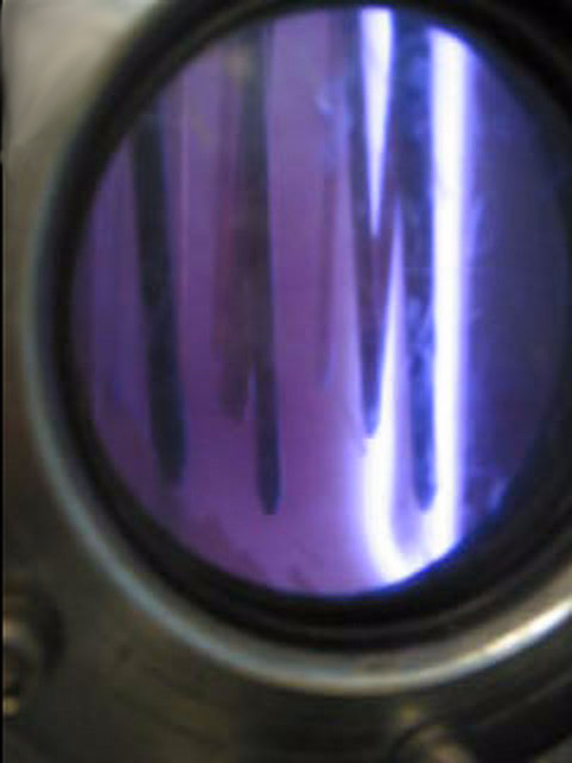 photo of viewing port of Surface Engineering Technologies coating chamber showing purple light