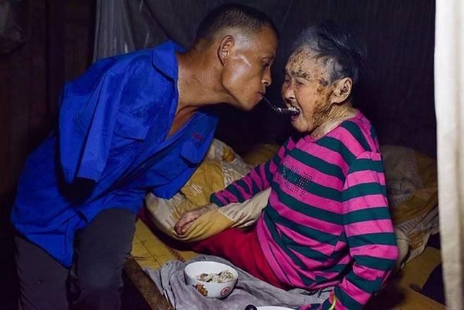 Sem ter os braços, homem usa dentes para alimentar sua mãe doente