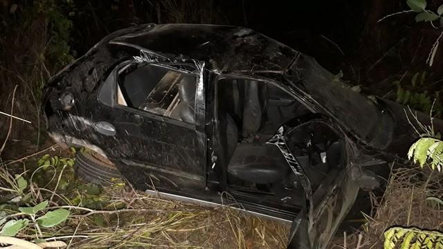 Duas pessoas ficam feridas após carro bater em caminhão, capotar e cair em ribanceira