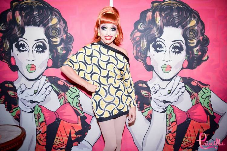 Bianca del Rio in Rio posing in front of her portraits by Suriani.