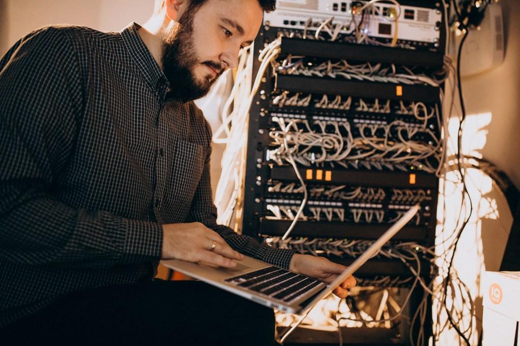 IT manager travaillant sur l'infrastructure des réseaux et de sécuritéd'une entreprise avec son ordi
