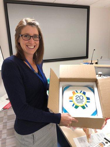Surpass Community member holding 20 million cake