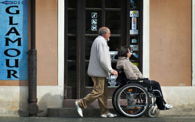 A man helping a person with woman disability | Prepping Tips For The Mobility Challenged