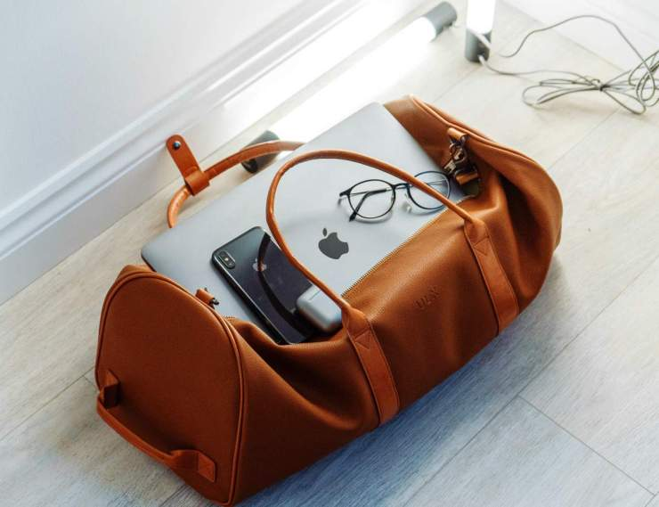 A silver MacBook and mobile phone in duffel bag preparedness us