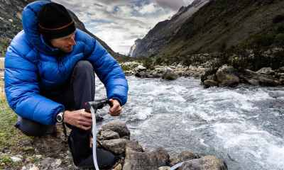 A man in blue down jacket filtering water for drinking from a river | How To Make A DIY Pocket Water Filter [Video] | Featured