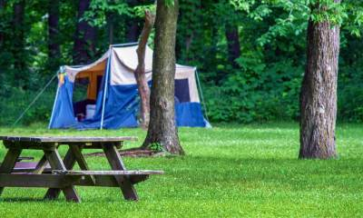 Feature | A tent is set up in an Indiana park, near a picnic table and a grove of tree | Best Campgrounds In Indiana