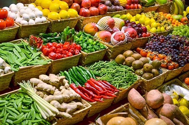 Stacks of fruits and vegetables in a grocery store produce section.