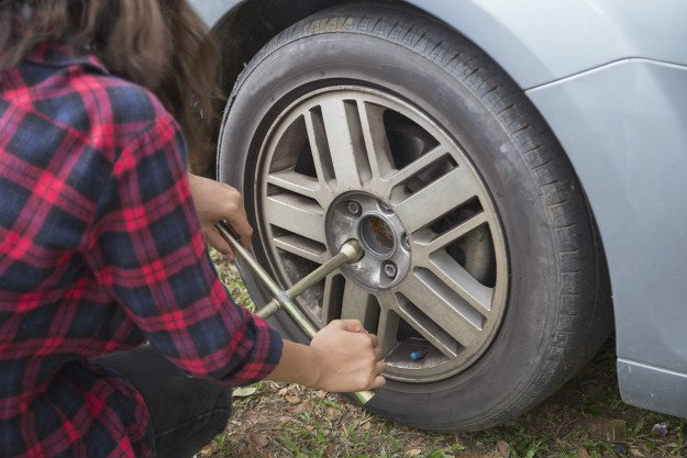 girl-changing-tire Survival Emergency Car Kit   The DIY Kit That Could Save Your Life