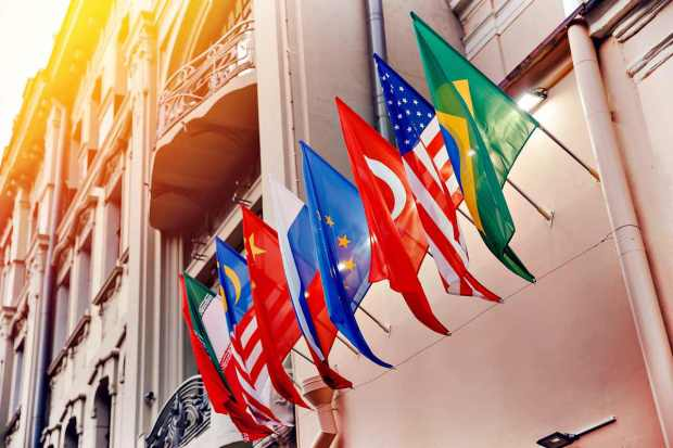 Flags of russia, united states, brazil, turkey, china, european union, iran on embassy house | Travel Safety Tips You Shouldn't Ignore