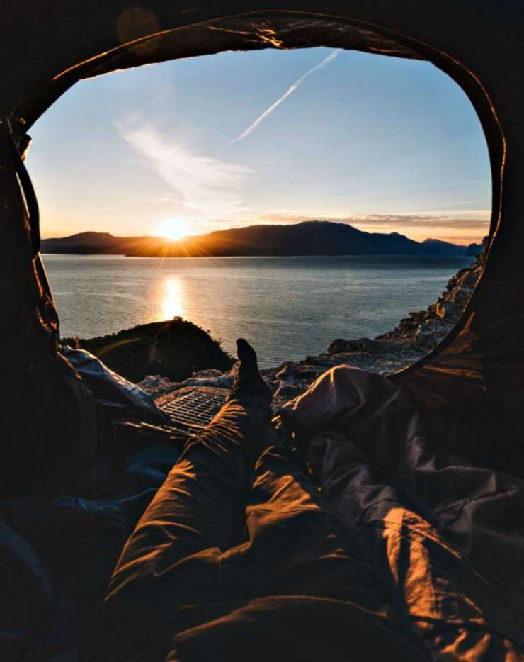 Person looking outside of a tent | Things You Need to Live Off the Grid