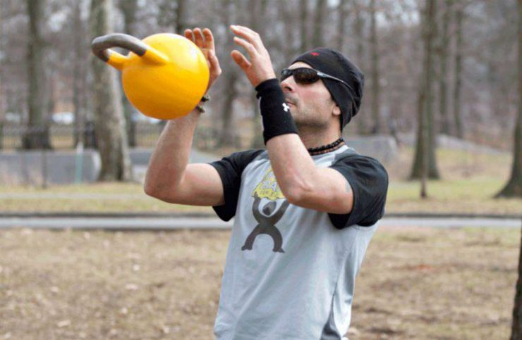 Man with yellow kettlebell in the park   Why The Kettlebell Is The Ultimate Tool For Physical Preparedness