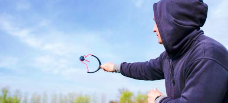 Man feeding fish with slingshot | How To Sight In A Slingshot And Score An Easy Meal