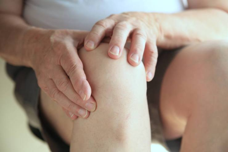 Older man has both hands on his sore knee   Survival Uses For Peppermint Oil