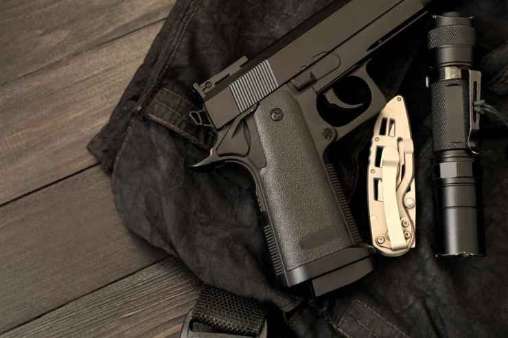 Handgun, knife, and flashlight on the wooden table | Tips To Stay Safe In A Crowd Or Riot