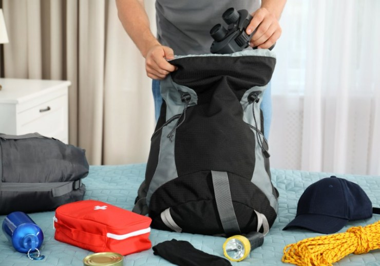 man packing different camping equipment into | incase city backpack