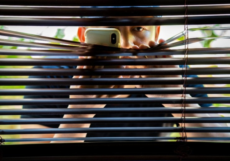 man sneaking venetian blind | home safety articles