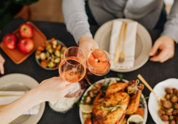 Food on the table with two people having wine | surviving christmas with the relatives