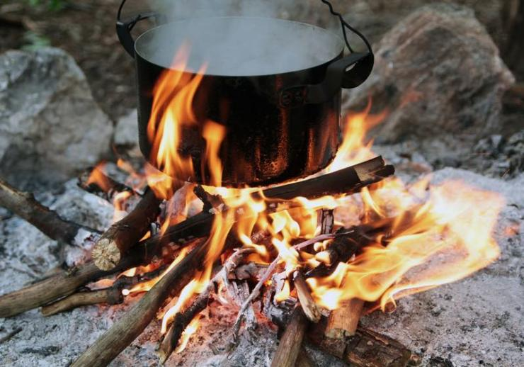 a pot of water boiling over a fire and a flame. Preparing food on campfire in wild camping | campfire cooking