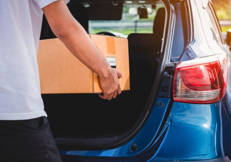 delivery man delivering cardboard box customers | living in your car hacks