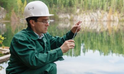 industrial ecologist or chemist takes a sample of water from lake at the site of a flooded mining pit | non potable water