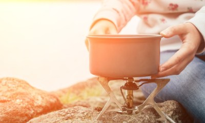Women's hands hold a saucepan on a gas burner-Wild Survival Foods-ss-featured