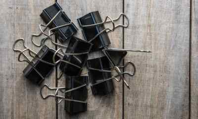 Binder Paper clip on old wooden background | INNOVATIVE WAYS TO USE BINDER CLIPS FOR SURVIVAL | Featured