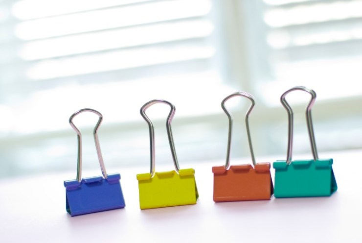 Colorful binder clip on white table near white window. long-tail clip-binder clips