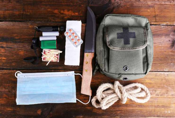 Emergency preparation equipment on wooden background-BUDGET SURVIVAL KIT