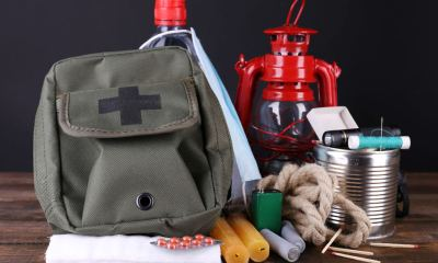 Emergency preparation equipment on wooden table, on dark background | Items to Pack in an Emergency Bag | featured
