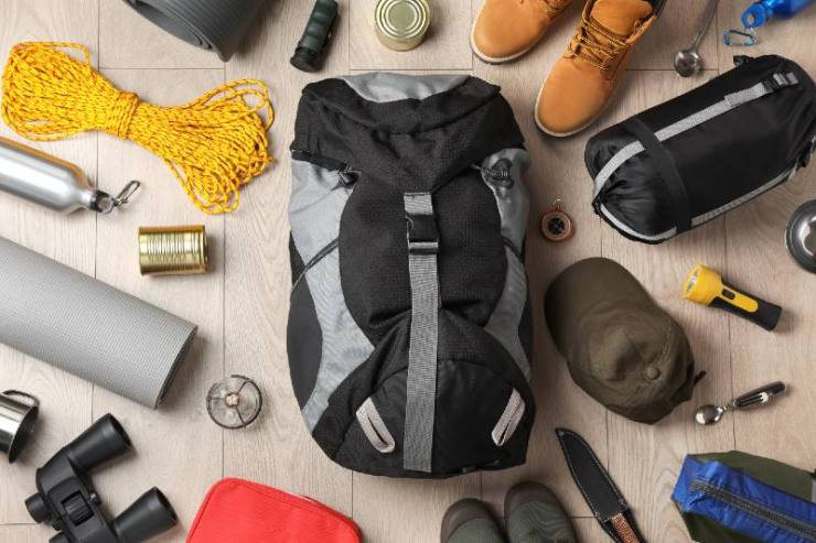 Flat lay composition with different camping equipment on wooden background-BUDGET SURVIVAL KIT