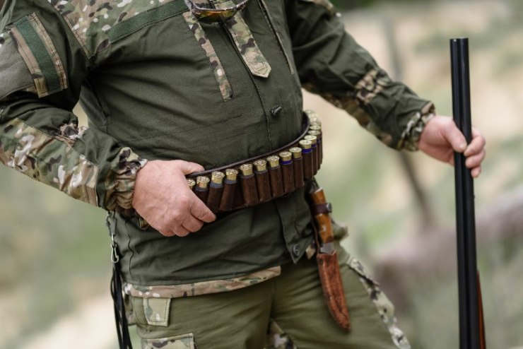 Hunter man stands with a belt of ammunition and a gun in his hands. A hunter with cartridges on his belt stands in the forest-battle belts