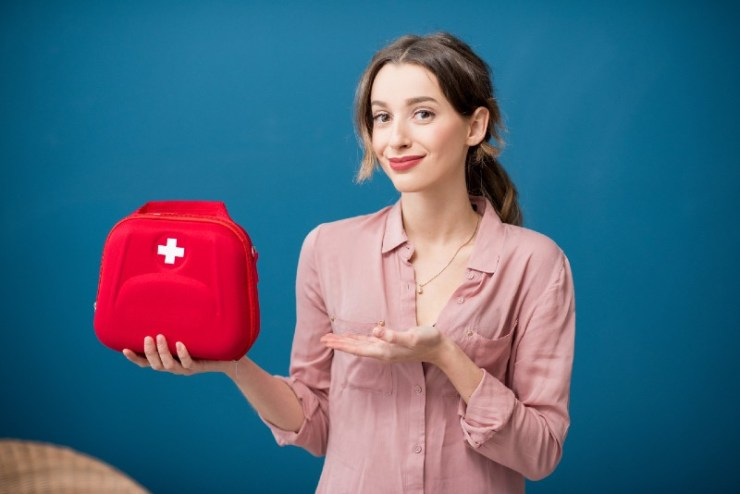 Portrait of a woman with first aid kit on the blue wall background-IFAK