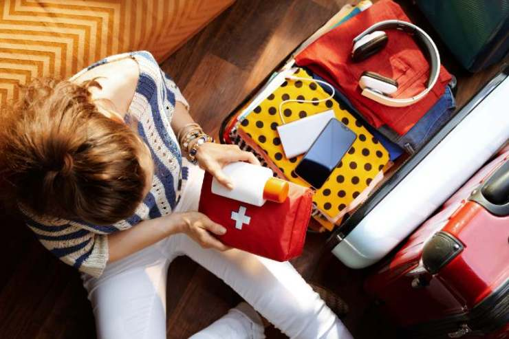 Upper view of modern woman in white pants and striped blouse at modern home in sunny summer day packing first aid kit-first aid kits