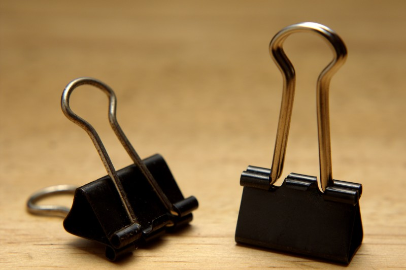 closeup of bulldog clips on wooden background-binder clips