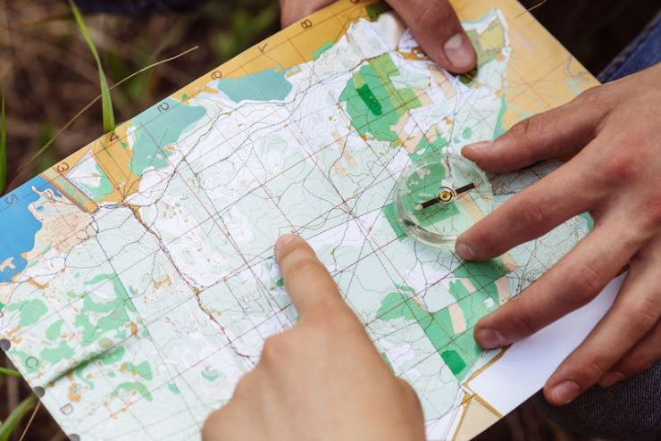two young tourists determine the route map and the compass what to pack in an emergency bag