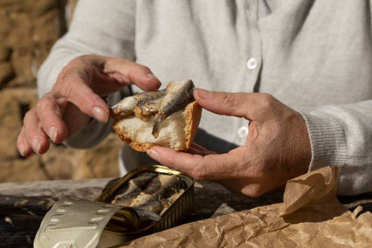 A senior woman, prepare a slice of bread with canned sardines to eat at the mountain hut-camping food on a budget