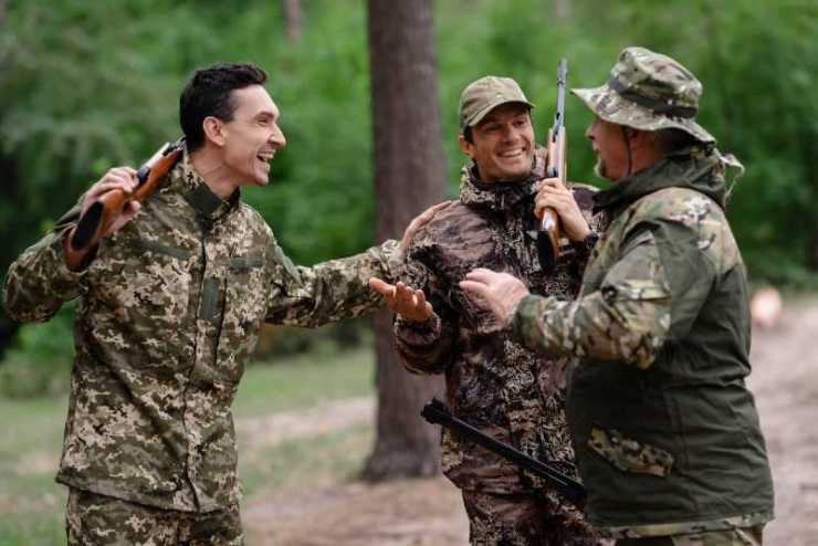 Hunters stand in the forest and discuss something together-summer hunting