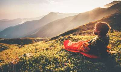 Man relaxing in sleeping bag enjoying sunset mountains landscape Travel Lifestyle campingHow to Choose A Sleeping Bag   featured