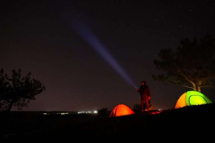 Man with bright flashlight near camping tents outdoors at night-Camping Without Electricity