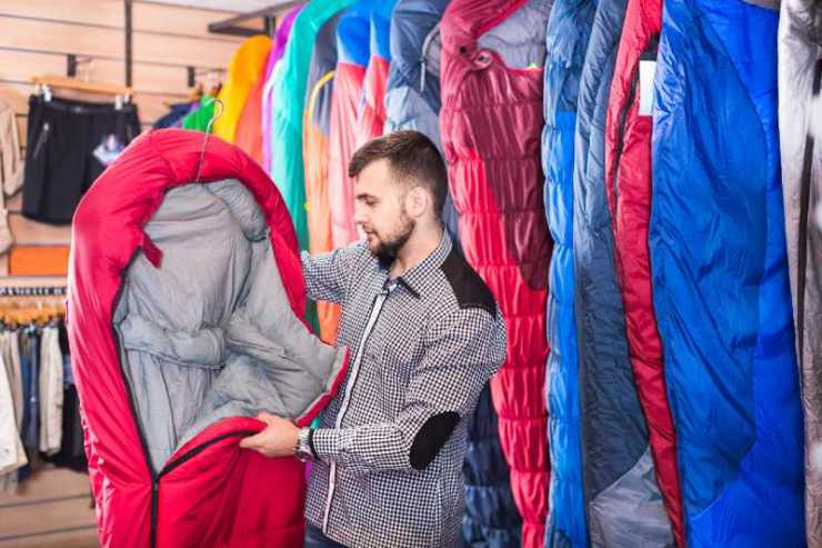 Smiling guy deciding on new sleeping bag at a sports equipment store-sleeping bag