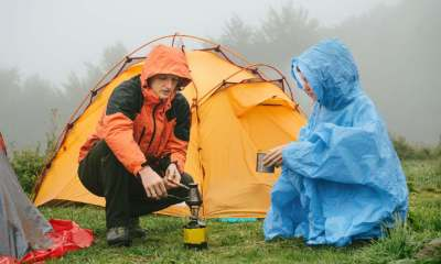 Tourists cooking coffee on primus near the tent in the mountains. Foggy and rainy camping while hiking | 5 Useful Tips For Camping In The Rain | featured