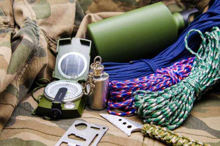 Travel accessories survival kit tools. Compass, metal flask, knife and colored paracord on the camouflage background-summer hunting