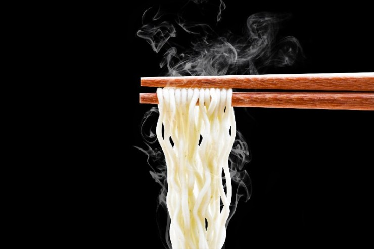 chopsticks noodles with smoke isolated on black background with clipping path-camping food hacks
