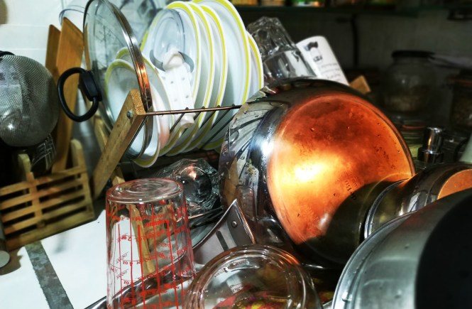 A pile of clean dishes drying on the rack
