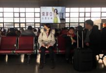 Warga Tiongkok mengenakan masker untuk mencegah tertular virus Corona.