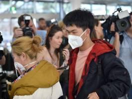 Para penumpang terakhir yang akan terbang meninggalkan Wuhan. ,Semuanya mengenakan masker. (Foto: CNA)