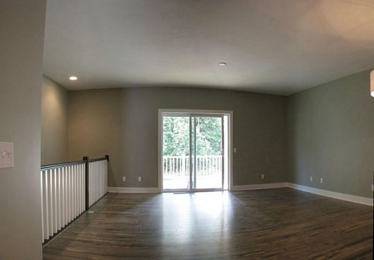 Main level living room with laminate floor, slider to covered deck, open stairway to lower level.